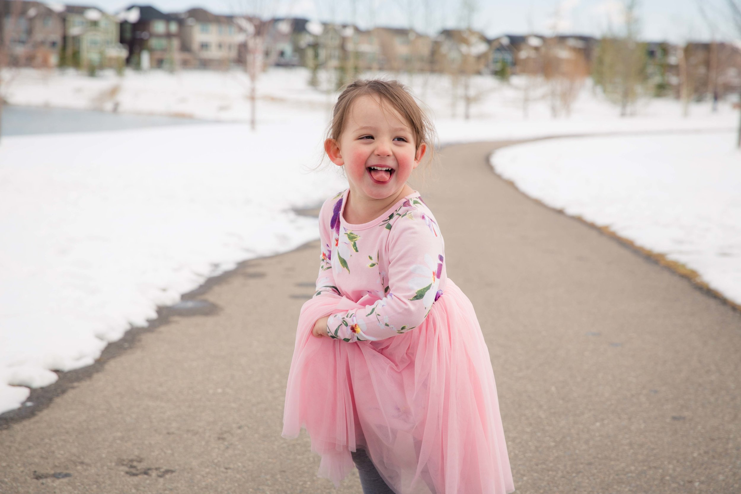 Happy little toddler girl is spinning around in her pink dress and sticking her tongue out. Calgary photographer.