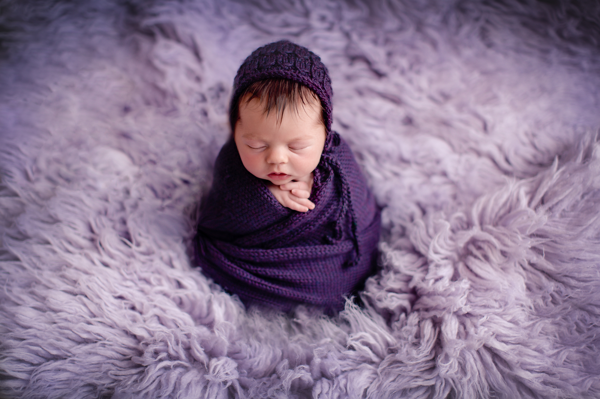 Potato sack pose. Newborn baby girl wrapped in purple wrap, wearing a purple hat and is posed on the lilac flokati rug.