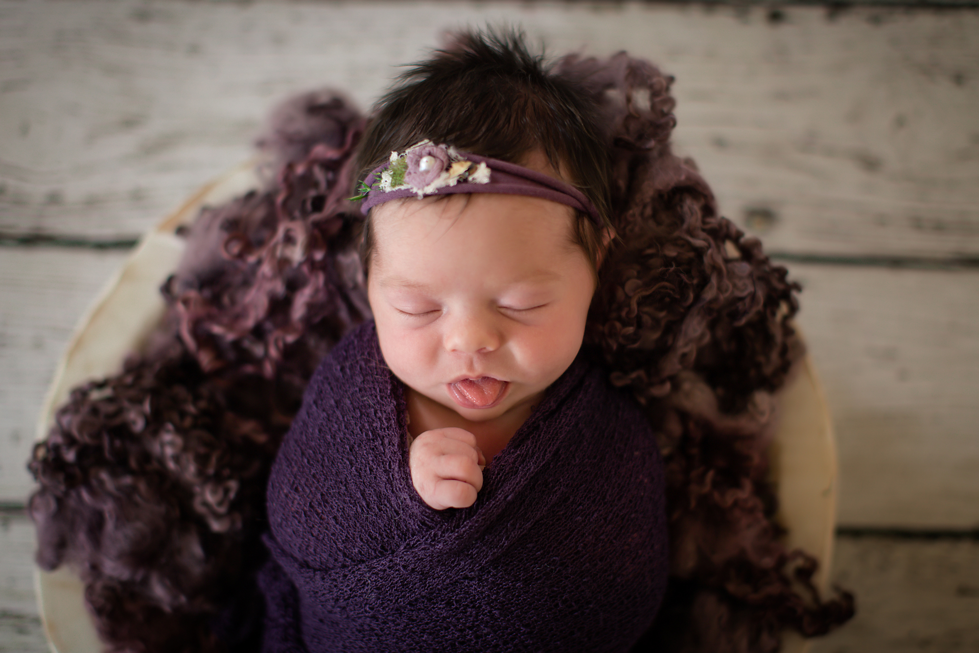 Newborn baby girl photoshoot idea. Baby girl is sticking out her tongue. Baby is posed in a bowl with purple fluff and wrapped in a purple wrap.