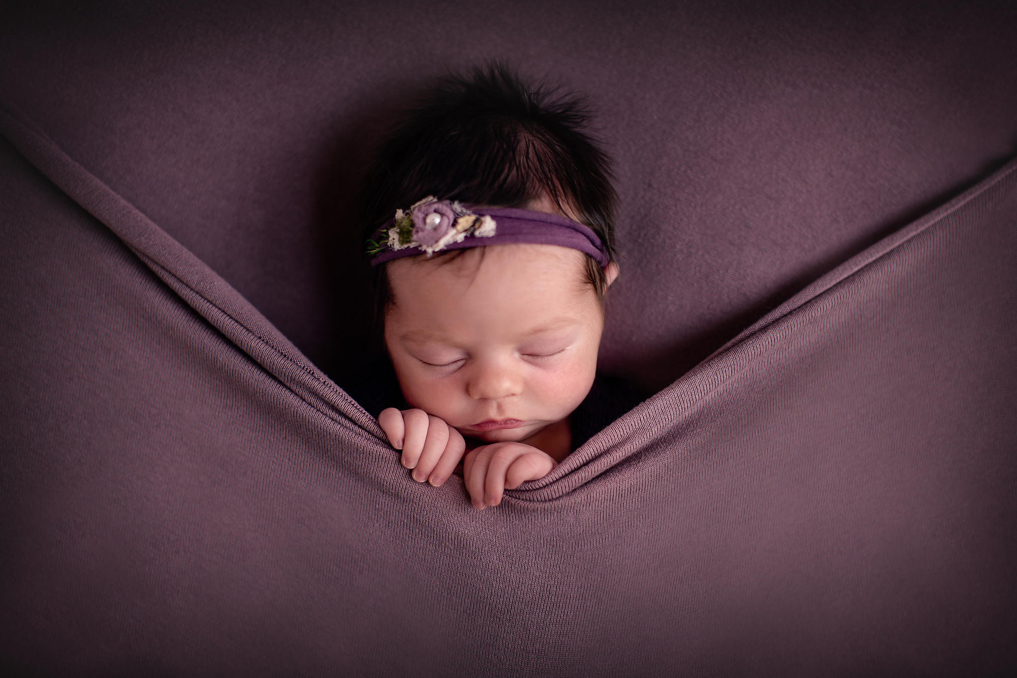 Newborn baby girl photoshoot idea. Baby girl is posed on a beanbag in this pick-a-boo pose.