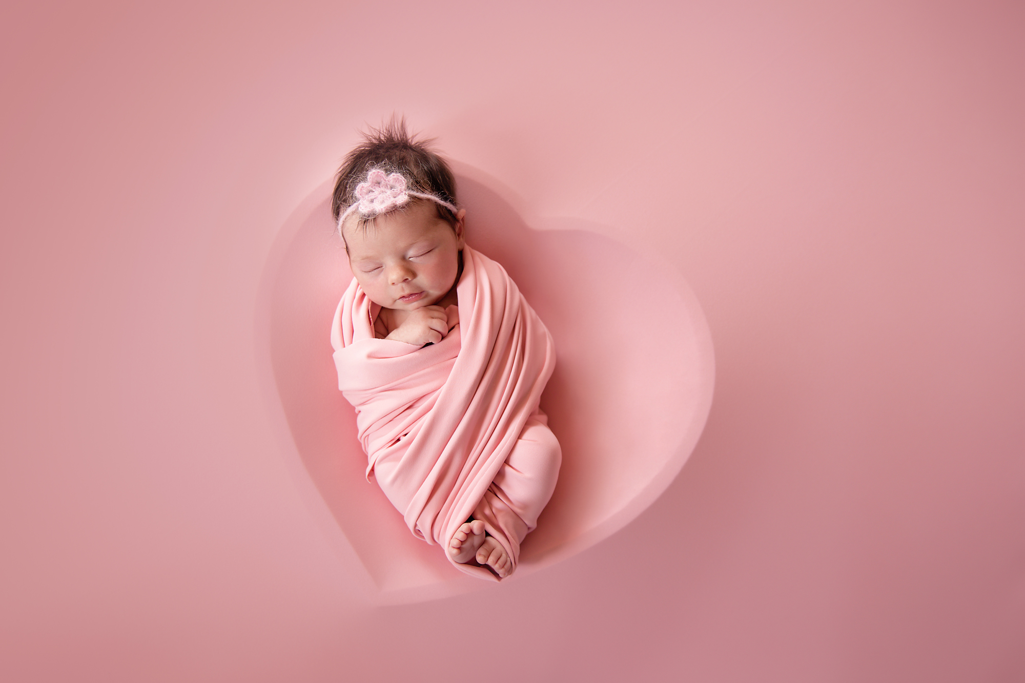 Newborn baby girl photoshoot idea. Baby girl is posed in a heart bowl covered by pink material. Calgary newborn photographer.