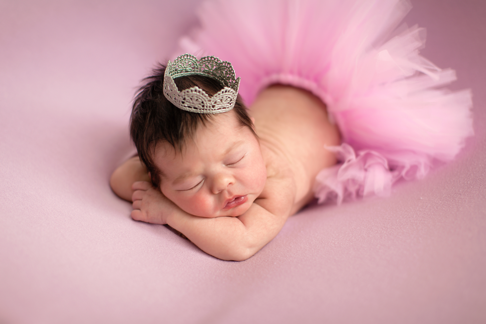 Newborn baby girl photoshoot idea. Tutu and a crown - baby girl is posed on a beanbag wearing a crown and a pink tutu. Calgary photographer