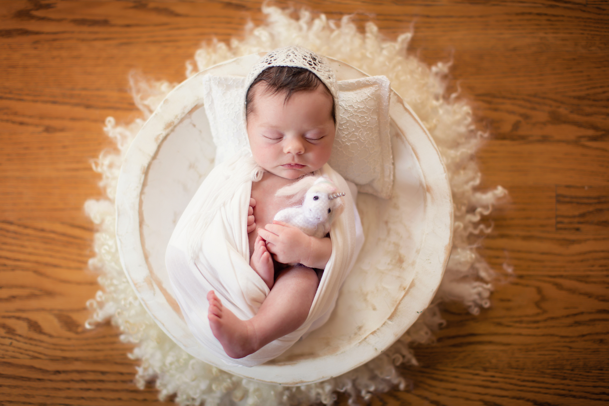 Newborn baby girl photoshoot idea. Calgary and Airdrie Newborn Photographer - Milashka Photography. Baby girl is wrapped in white and is holding a unicorn in a white bowl.