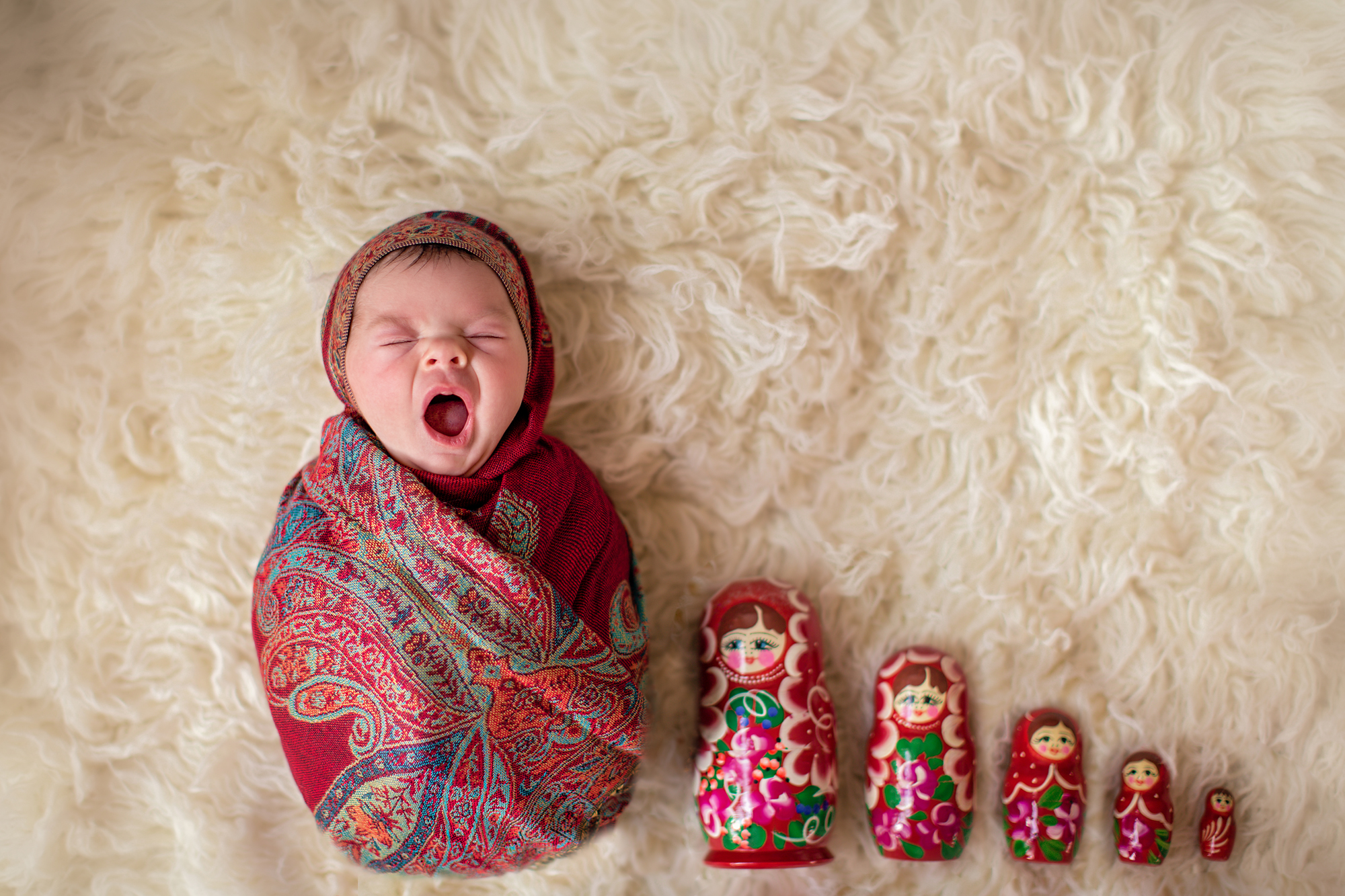 Newborn baby girl photoshoot idea. Calgary and Airdrie Newborn Photographer - Milashka Photography. Matryoshka - Russian doll shot. Baby girl is wrapped like a Matryoshka (Russian doll) and have the rest of the matryoshka's beside her.