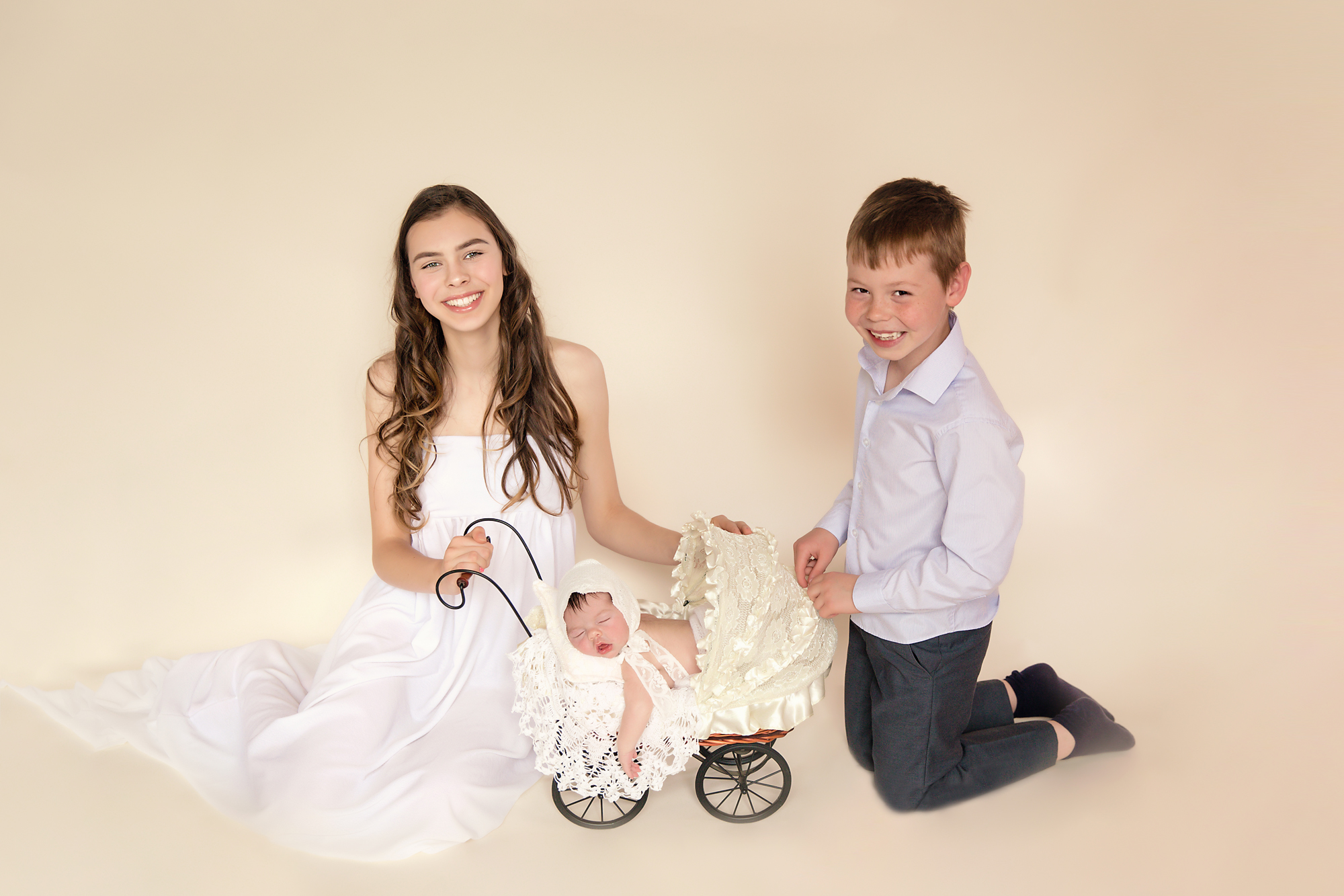 Newborn baby girl photoshoot idea. Calgary and Airdrie Newborn Photographer - Milashka Photography. Siblings are sitting beside a little stroller with their baby sister in it.