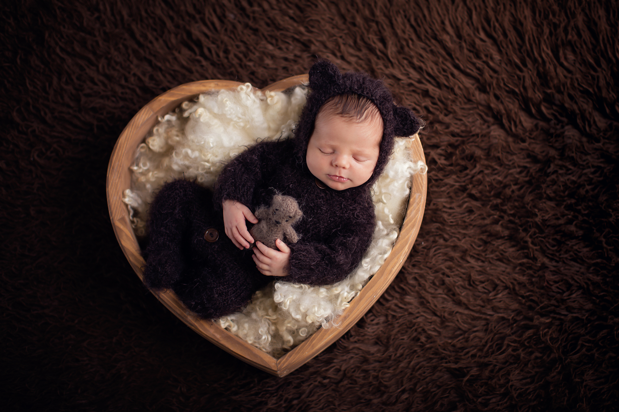 Newborn baby boy photoshoot ideas. Calgary and Airdrie newborn baby photographer - Milashka Photography. Baby boy is dressed in a bear onesie and is holding a little bear toy and is sleeping in a heart bowl.