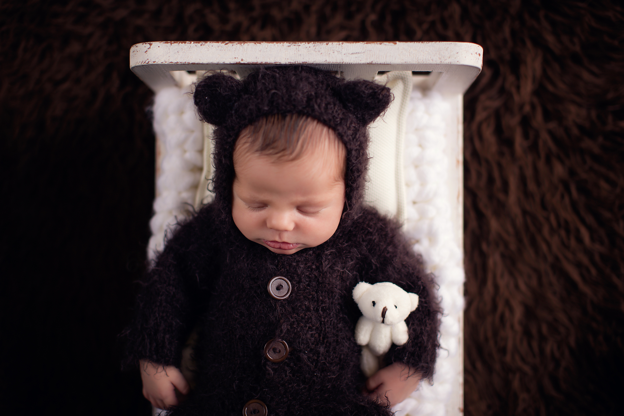 Newborn baby boy photoshoot ideas. Calgary and Airdrie newborn baby photographer - Milashka Photography. Little baby boy is wearing a bear outfit  and is holding a little bear, he is sleeping soundly on a little bed.