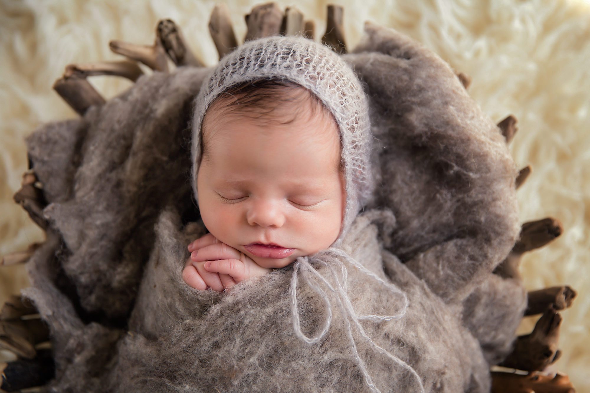 Newborn baby boy photoshoot ideas. Calgary and Airdrie newborn baby photographer - Milashka Photography. Game of Thrones inspired shot. Baby boy is sleeping soundly in a basket.
