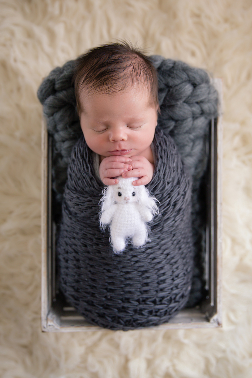 Newborn baby boy photoshoot ideas. Calgary and Airdrie newborn baby photographer - Milashka Photography. Baby boy is wrapped in a grey wrap and is posed in a white crate.