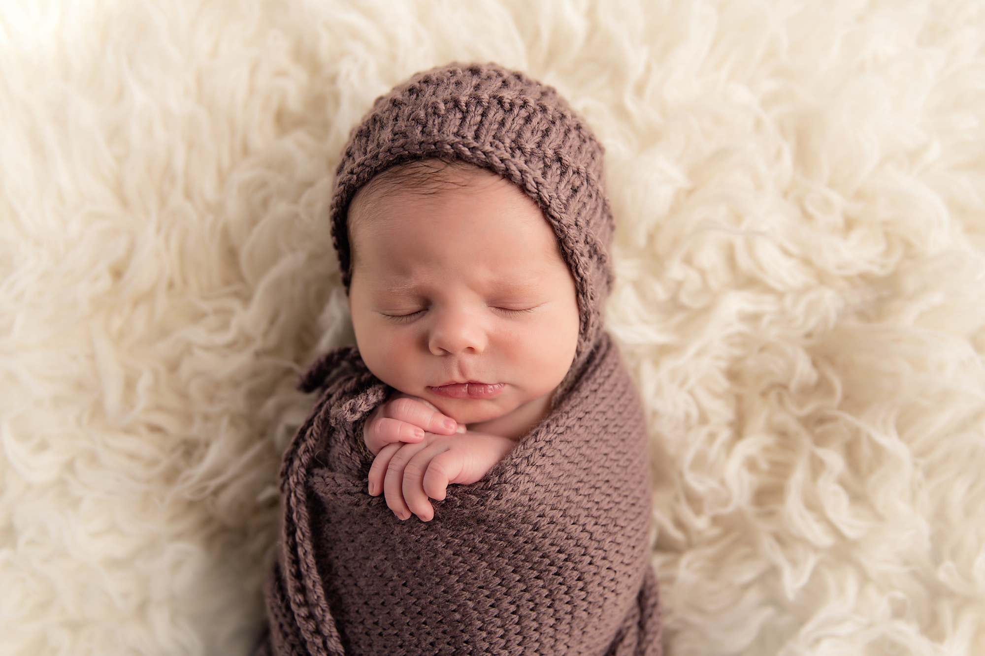 Newborn baby boy photoshoot ideas. Calgary and Airdrie newborn baby photographer - Milashka Photography. Baby boy is posed on a flokati rug wearing a brown hat and wrap.