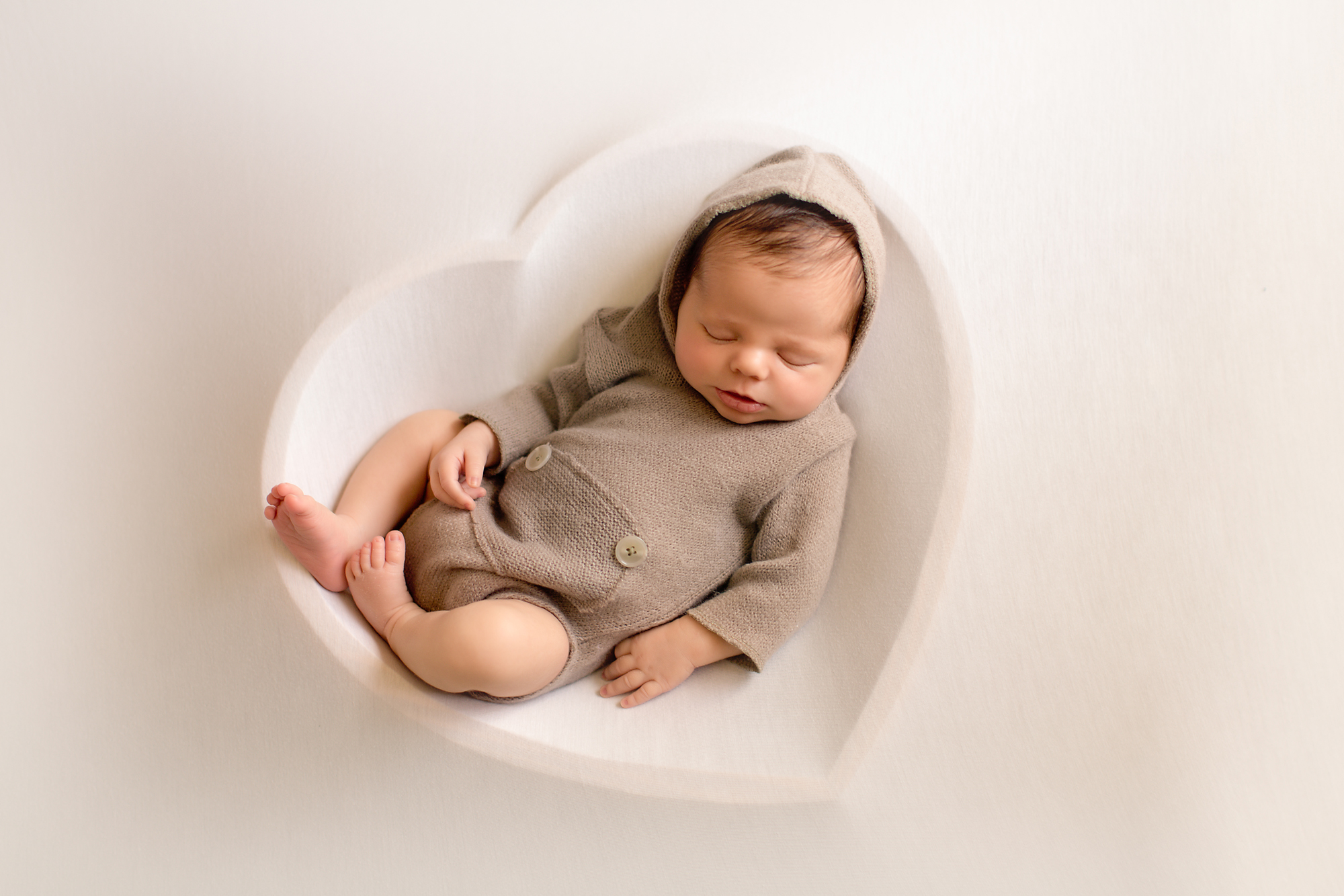 Newborn baby boy photoshoot ideas. Calgary and Airdrie newborn baby photographer - Milashka Photography. Baby boy is posed in a heart bowl.