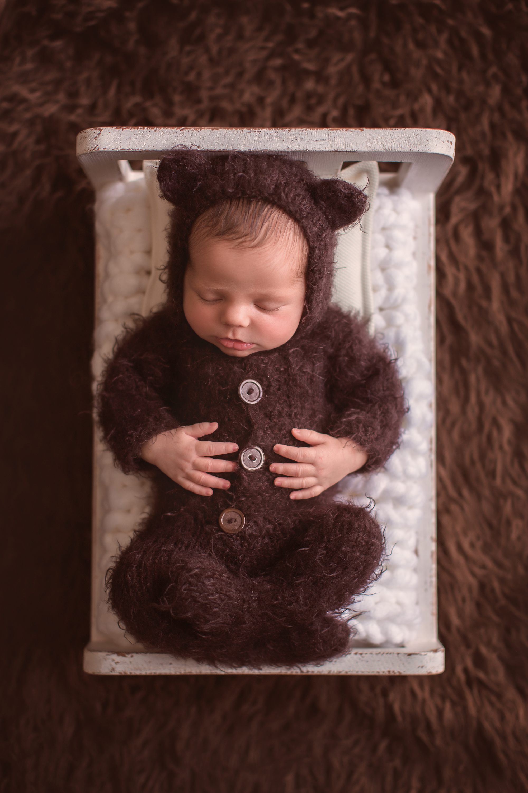 Newborn baby boy photoshoot ideas. Calgary and Airdrie newborn baby photographer - Milashka Photography. Newborn baby boy is dressed in a bear onesie and is sleeping soundly on a little bed.