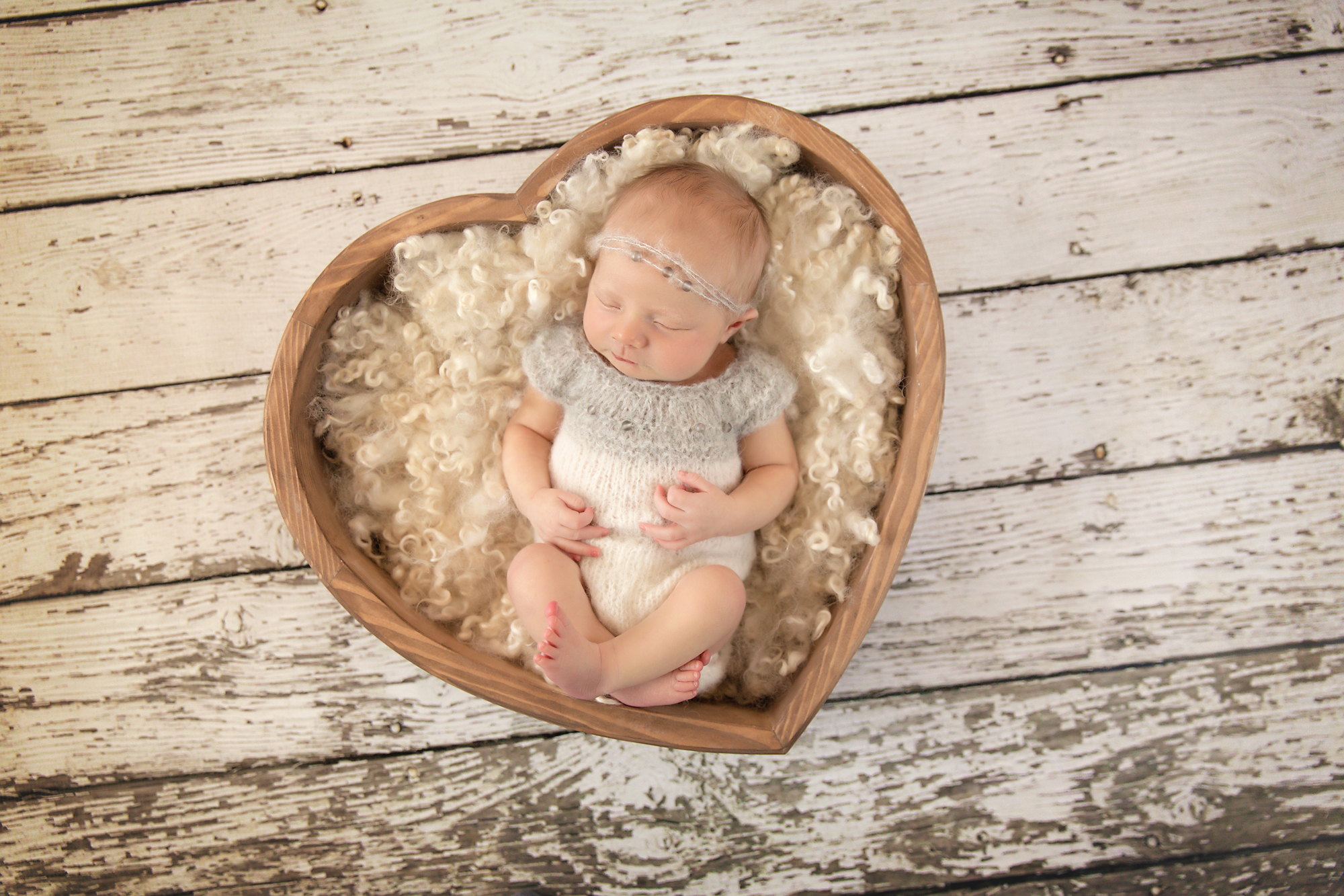 Newborn Photoshoot inspiration ideas. Calgary and Airdrie, Alberta Newborn and Baby photographer - Milashka Photography. Baby girl is posed in a heart shaped wooden bowl and is wearing a cute little grey and white knitted outfit.