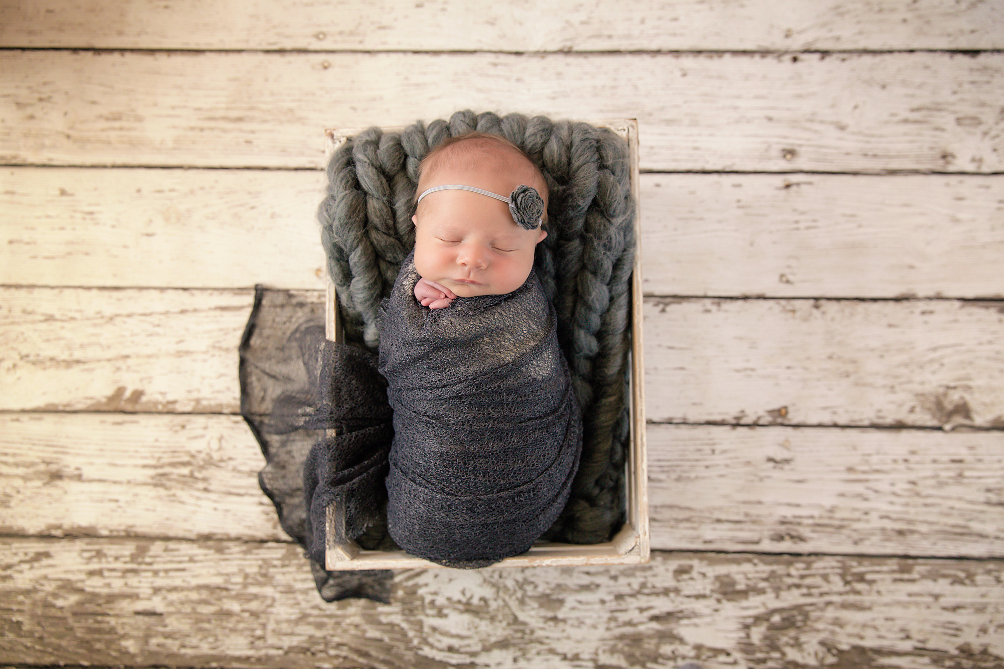 Newborn Photoshoot inspiration ideas. Calgary and Airdrie, Alberta Newborn and Baby photographer - Milashka Photography. Baby girl is wrapped in a grey wrap and is posed in a white crate.