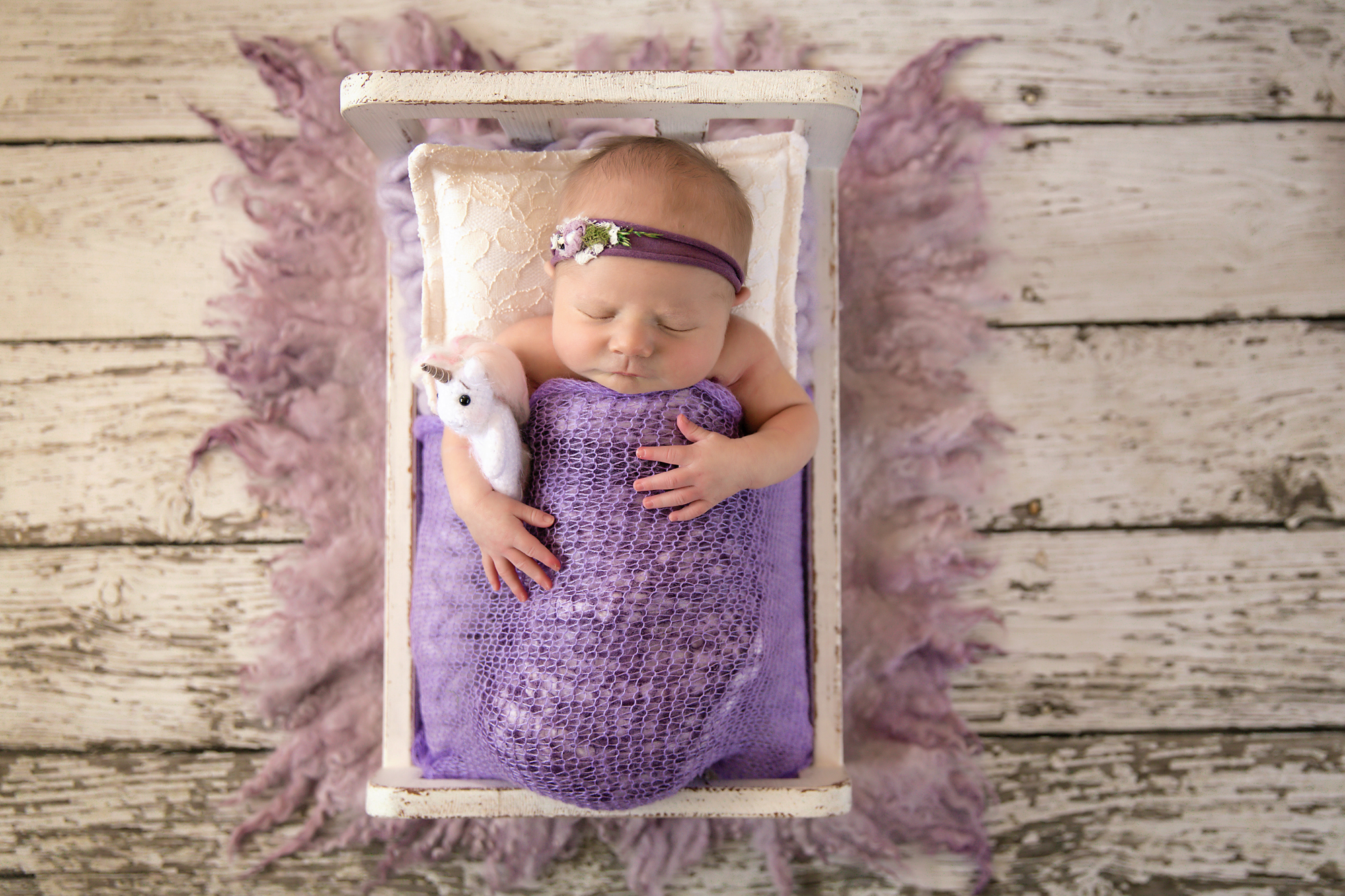 Newborn Photoshoot inspiration ideas. Calgary and Airdrie, Alberta Newborn and Baby photographer - Milashka Photography. Baby girl is wrapped in a lilac wrap and is posed on a little white wooden bed and is holding a unicorn.