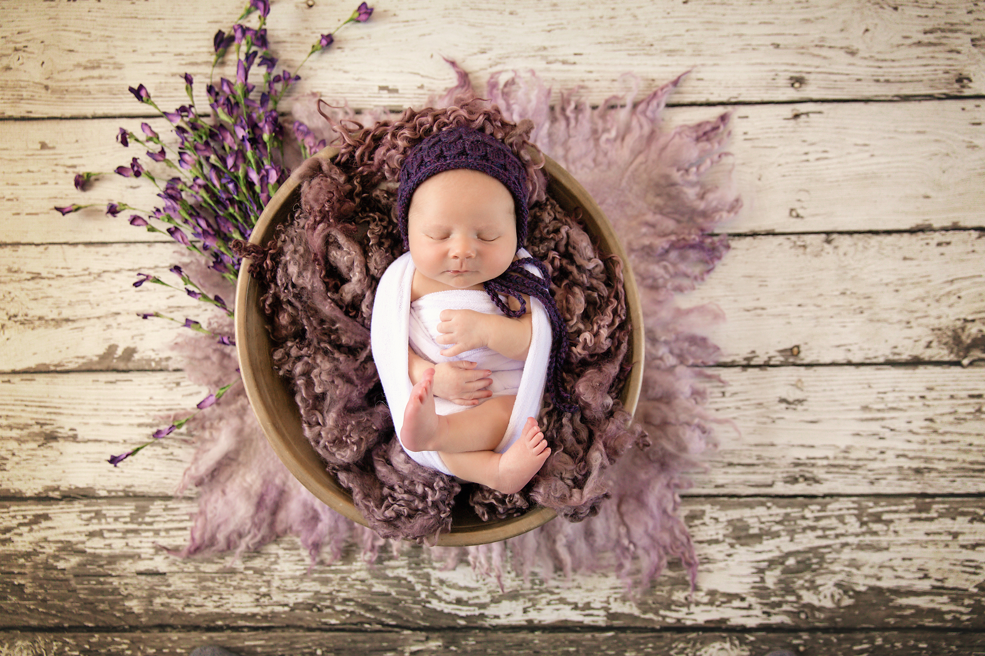 Newborn Photoshoot inspiration ideas. Calgary and Airdrie, Alberta Newborn and Baby photographer - Milashka Photography. Baby girl is posed in a wooden bowl and surrounded by purple flowers and fluff and is wearing a purple hat.
