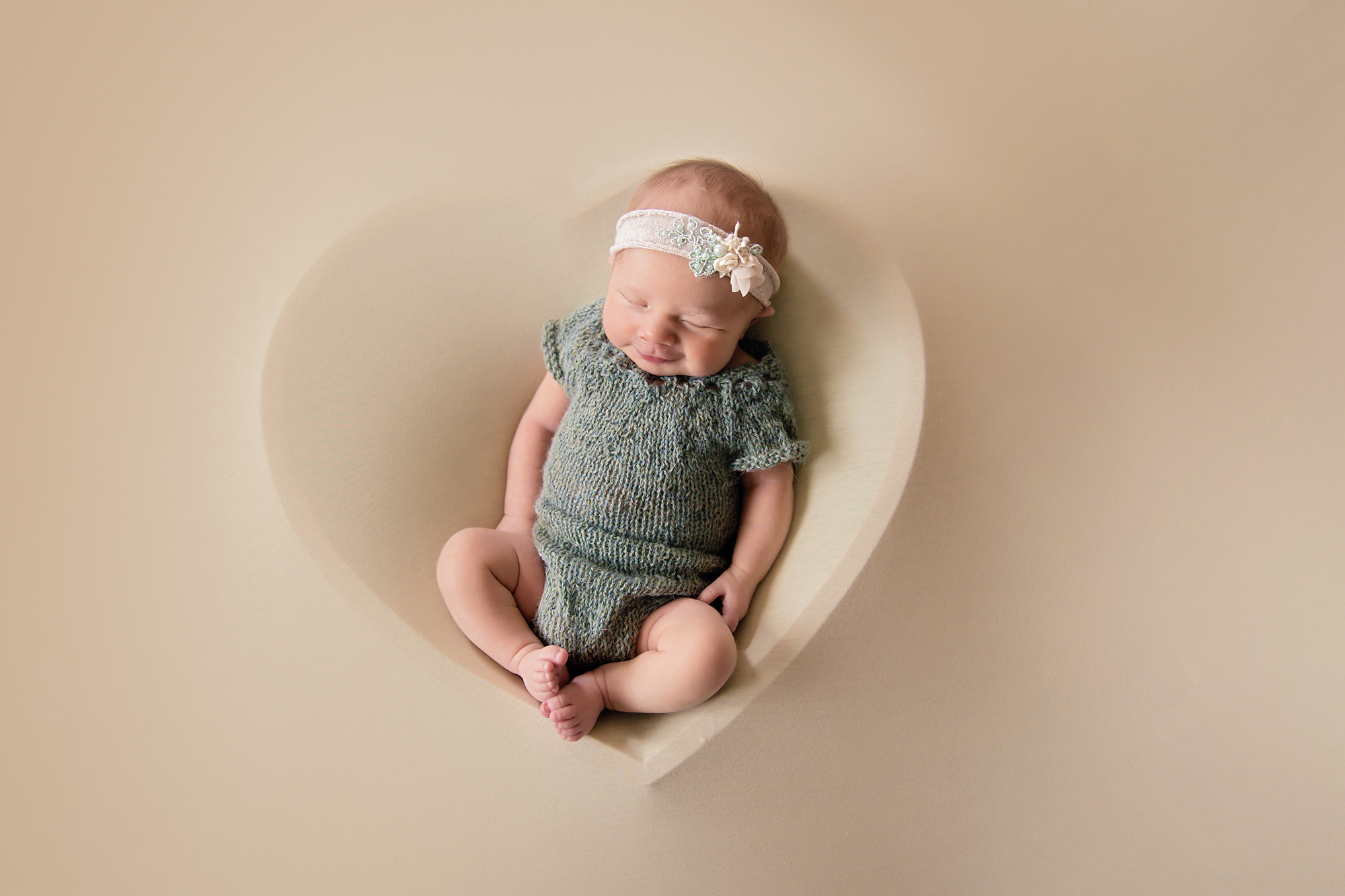 Newborn Photoshoot inspiration ideas. Calgary and Airdrie, Alberta Newborn and Baby photographer - Milashka Photography. Baby girl is posed in a heart bowl covered by a backdrop and is wearing a cute green outfit.