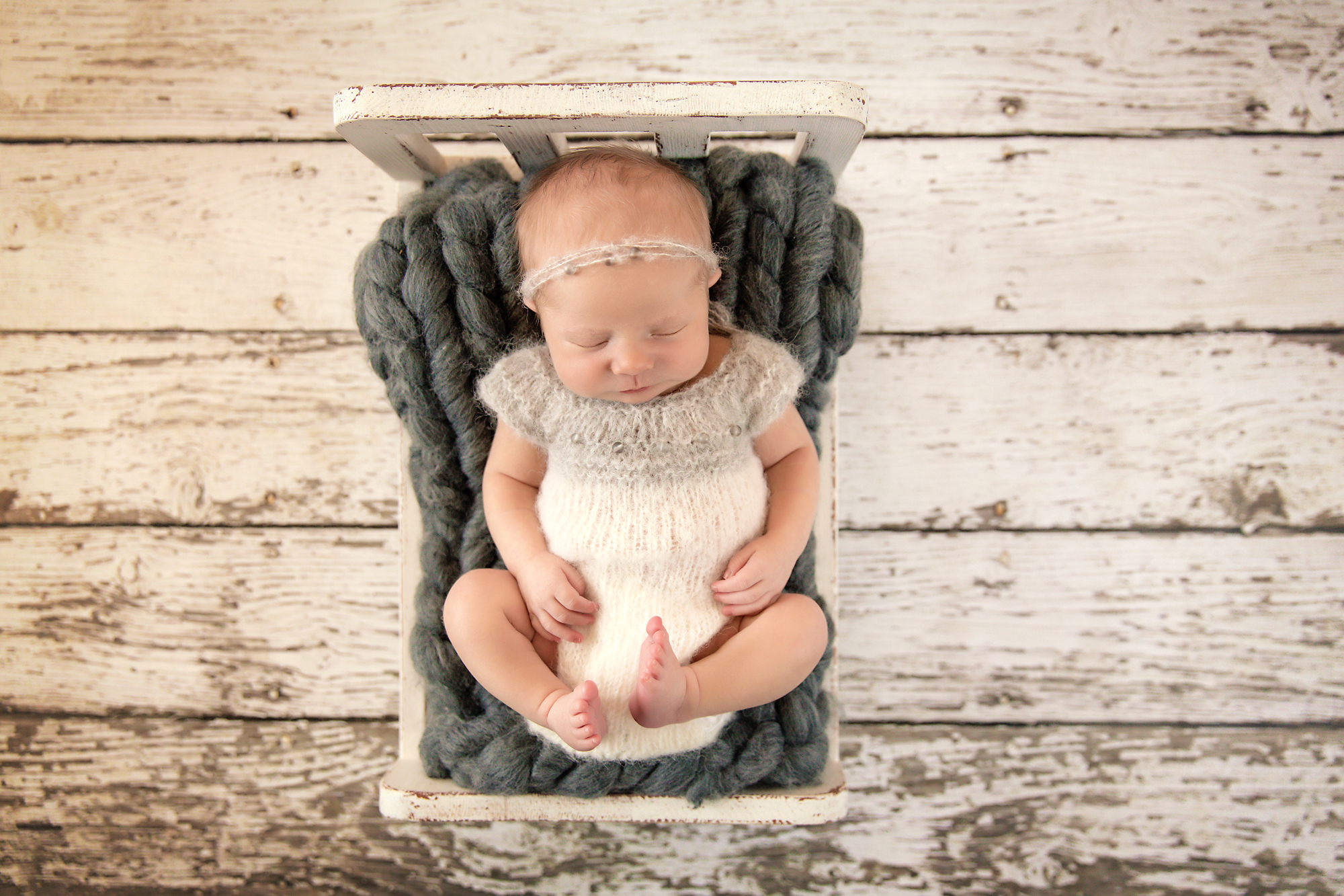 Newborn Photoshoot inspiration ideas. Calgary and Airdrie, Alberta Newborn and Baby photographer - Milashka Photography. Baby girl is posed on a wooden white bed and is propped by a grey bump blanket and is wearing a cute white and grey knitted outfit.