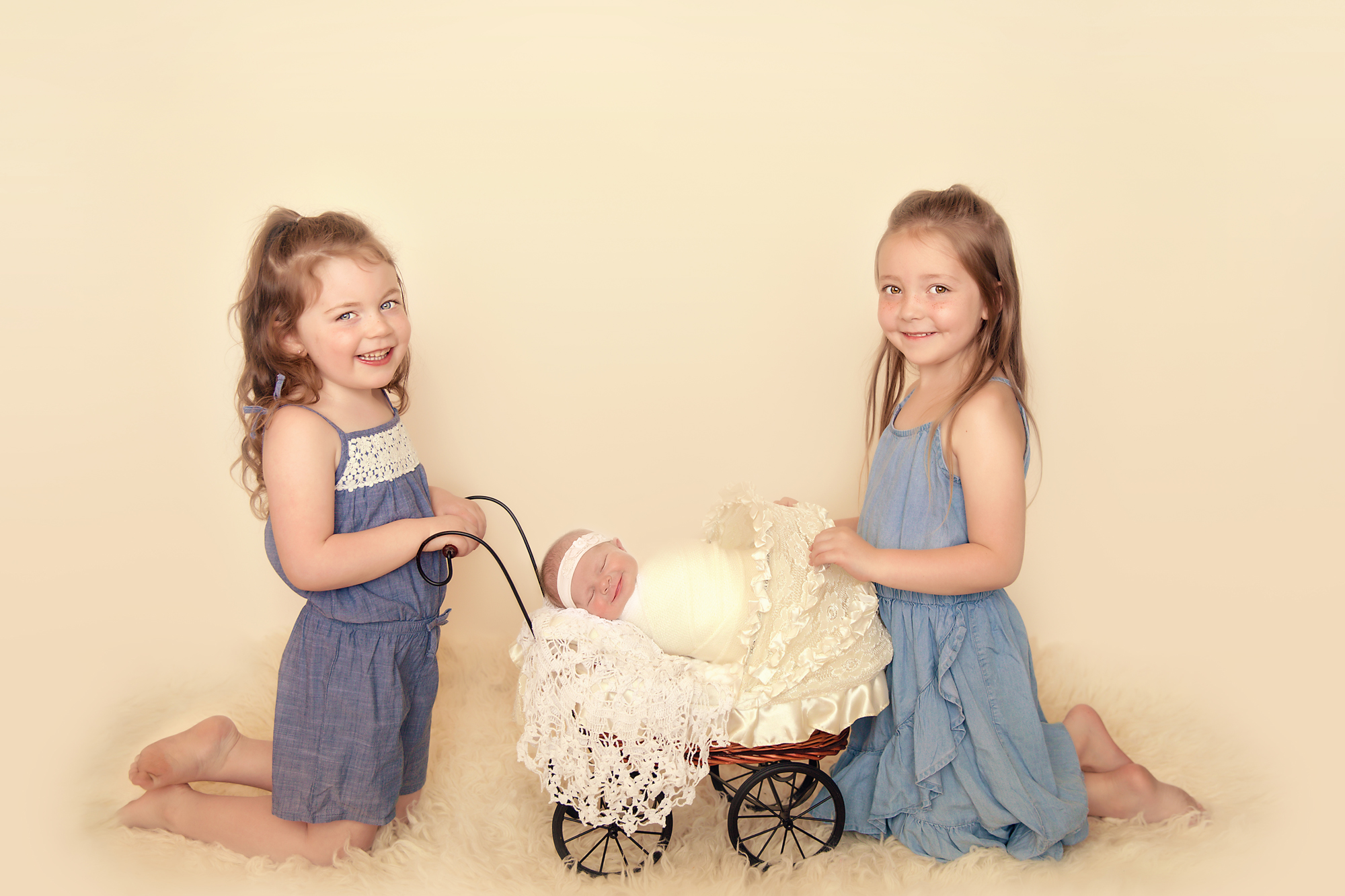 Newborn Photoshoot inspiration ideas. Calgary and Airdrie, Alberta Newborn and Baby photographer - Milashka Photography. Siblings shot - 2 sisters are holding a little pram where their newborn baby sister is sleeping. All 3 sisters are smiling.
