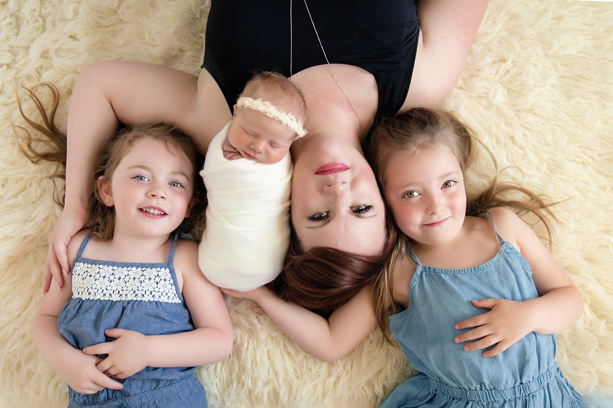 Newborn Photoshoot inspiration ideas. Calgary and Airdrie, Alberta Newborn and Baby photographer - Milashka Photography. Mom and 3 daughters are posed on a beanbag and flokati rug.