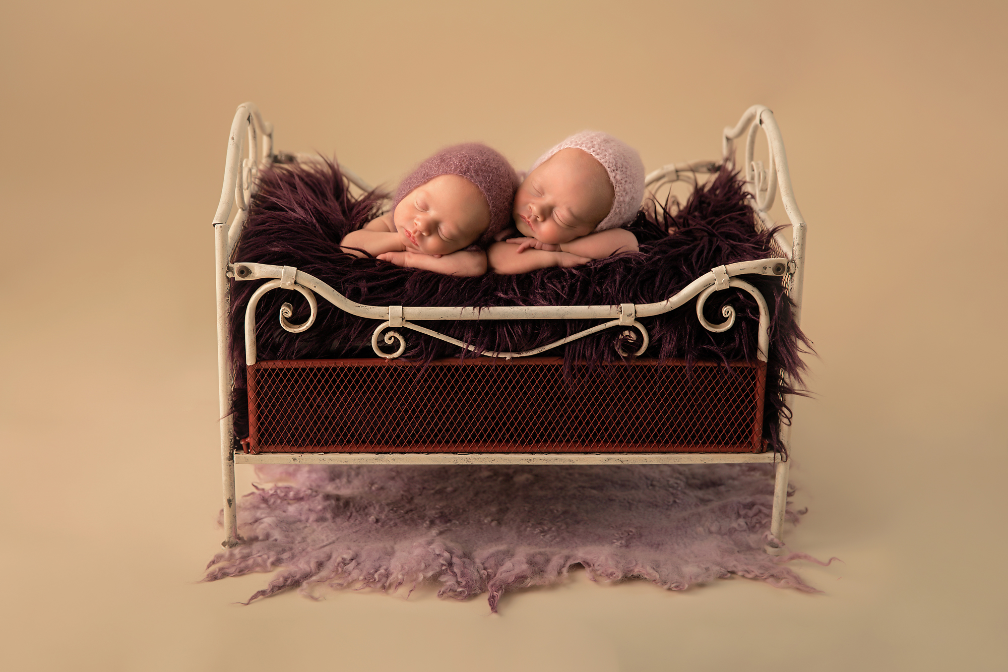 Identical Newborn Baby Sisters. Calgary photoshoot with Milashka Photography. Two newborn twin sisters are posed in the antique bed with purple rug and wearing purple bonnets.