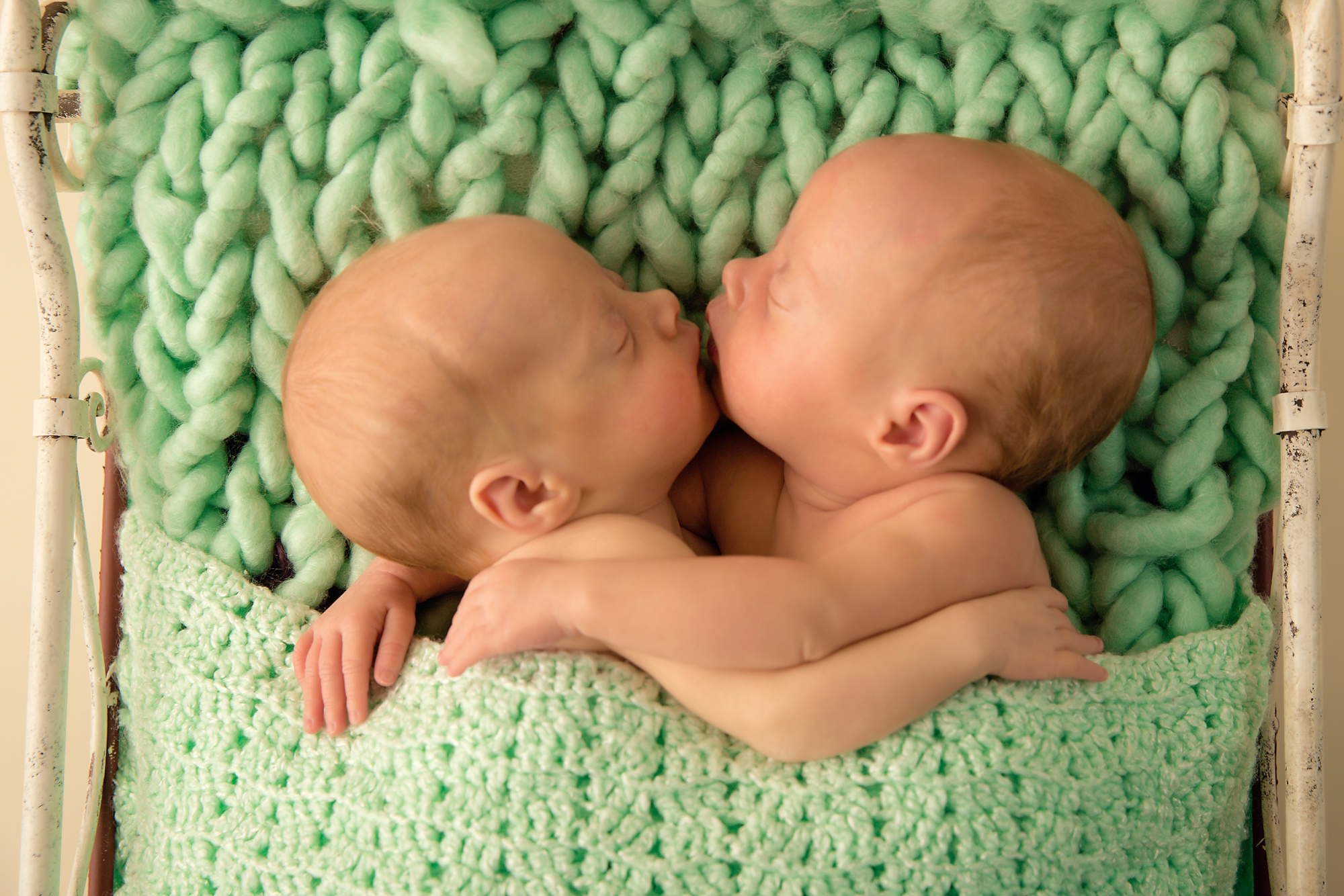 Twin sisters are giving each other a kiss pose. Twins Photography in Calgary, Alberta by Milashka Photography.