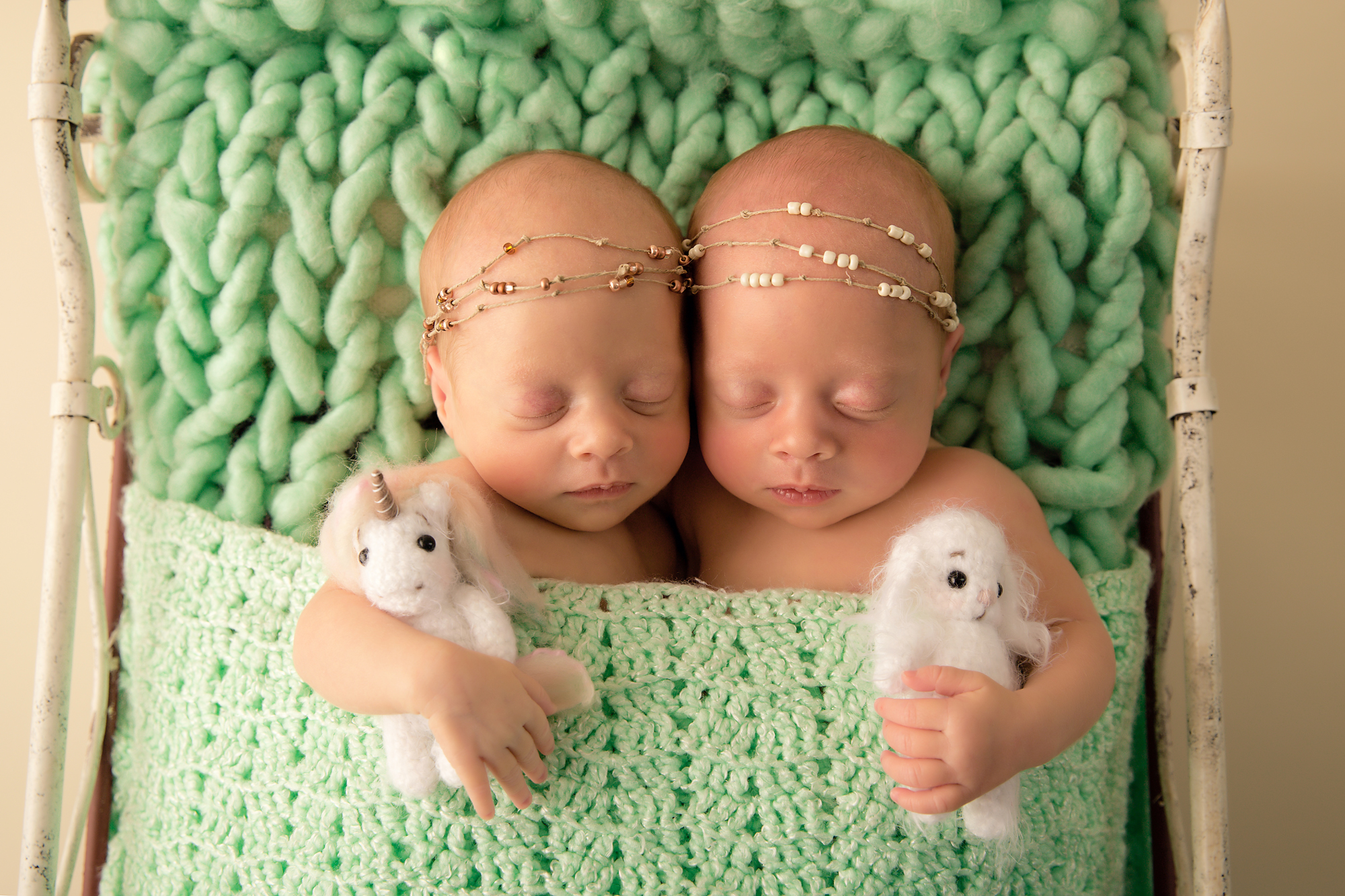 Twins Photography in Calgary, Alberta by Milashka Photography. Twin sisters are holding cute little toys in their hands and sleeping soundly on an antique bed