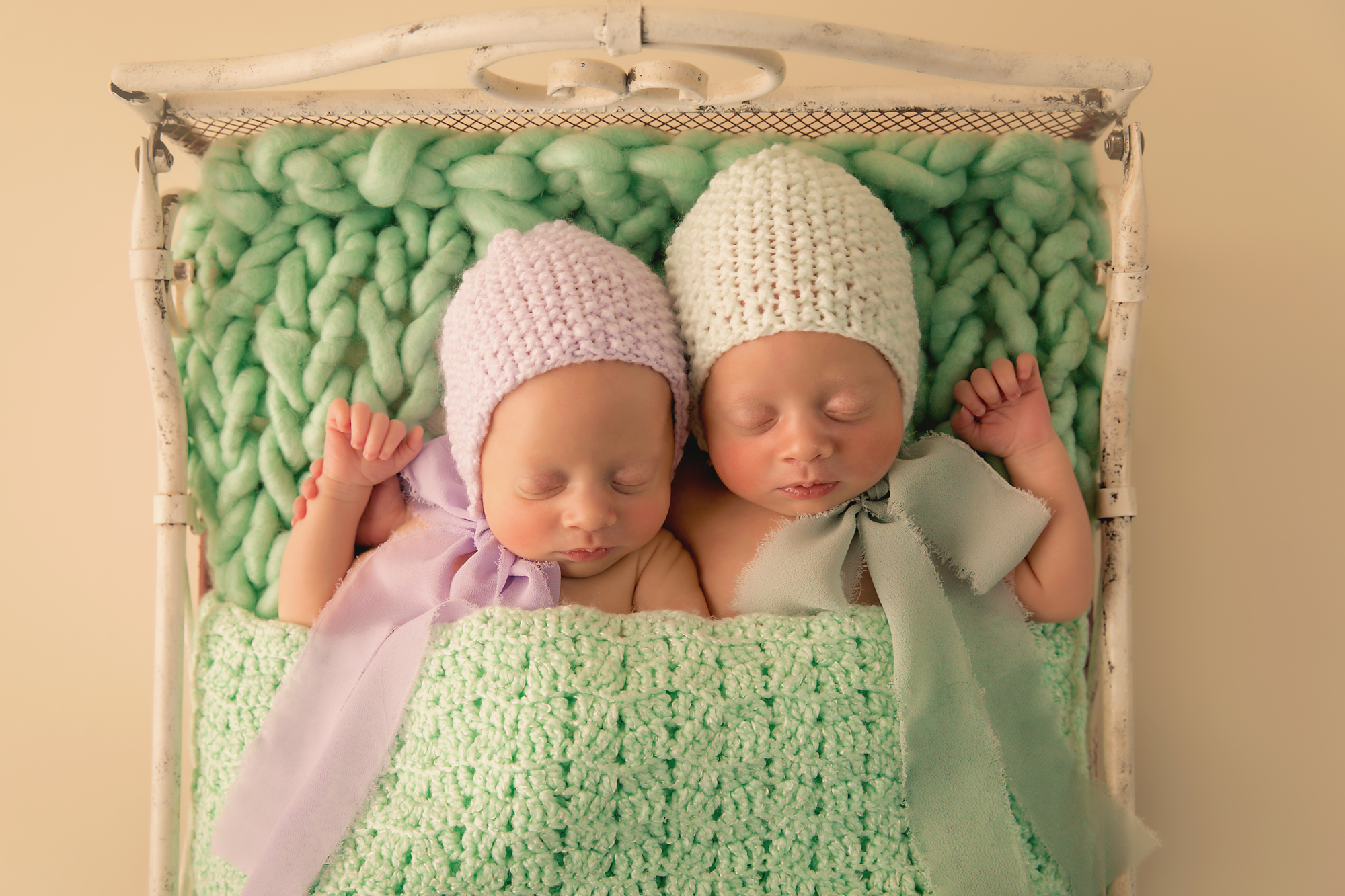 Twins Photography in Calgary, Alberta by Milashka Photography. Twin sisters are sleeping soundly and wearing cute lilac and lime hats