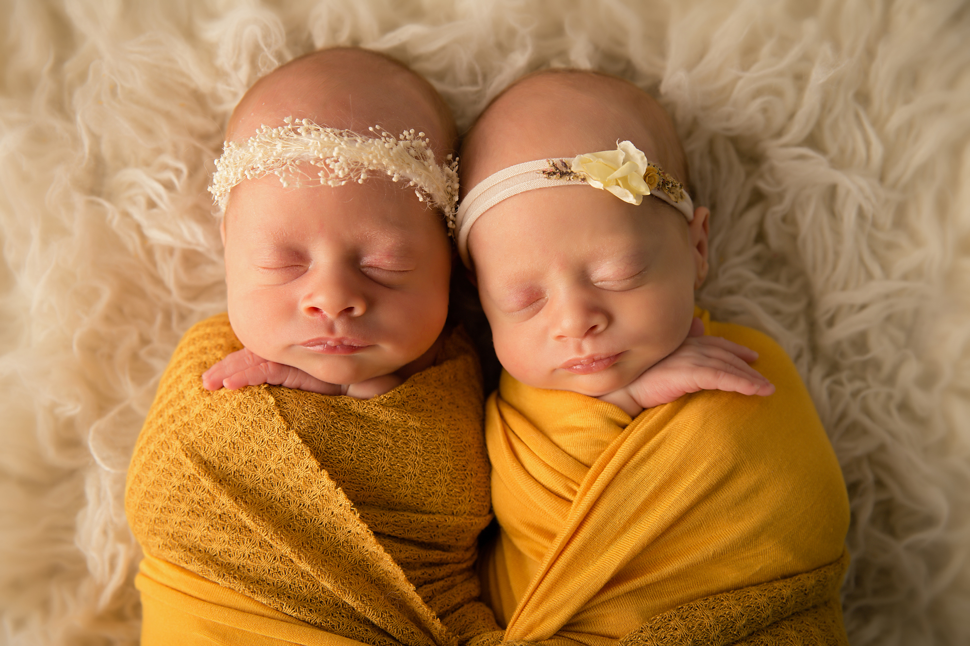 Twins Photography in Calgary, Alberta by Milashka Photography. Twin sisters are lying side by side wrapped in the mustard colour wraps.