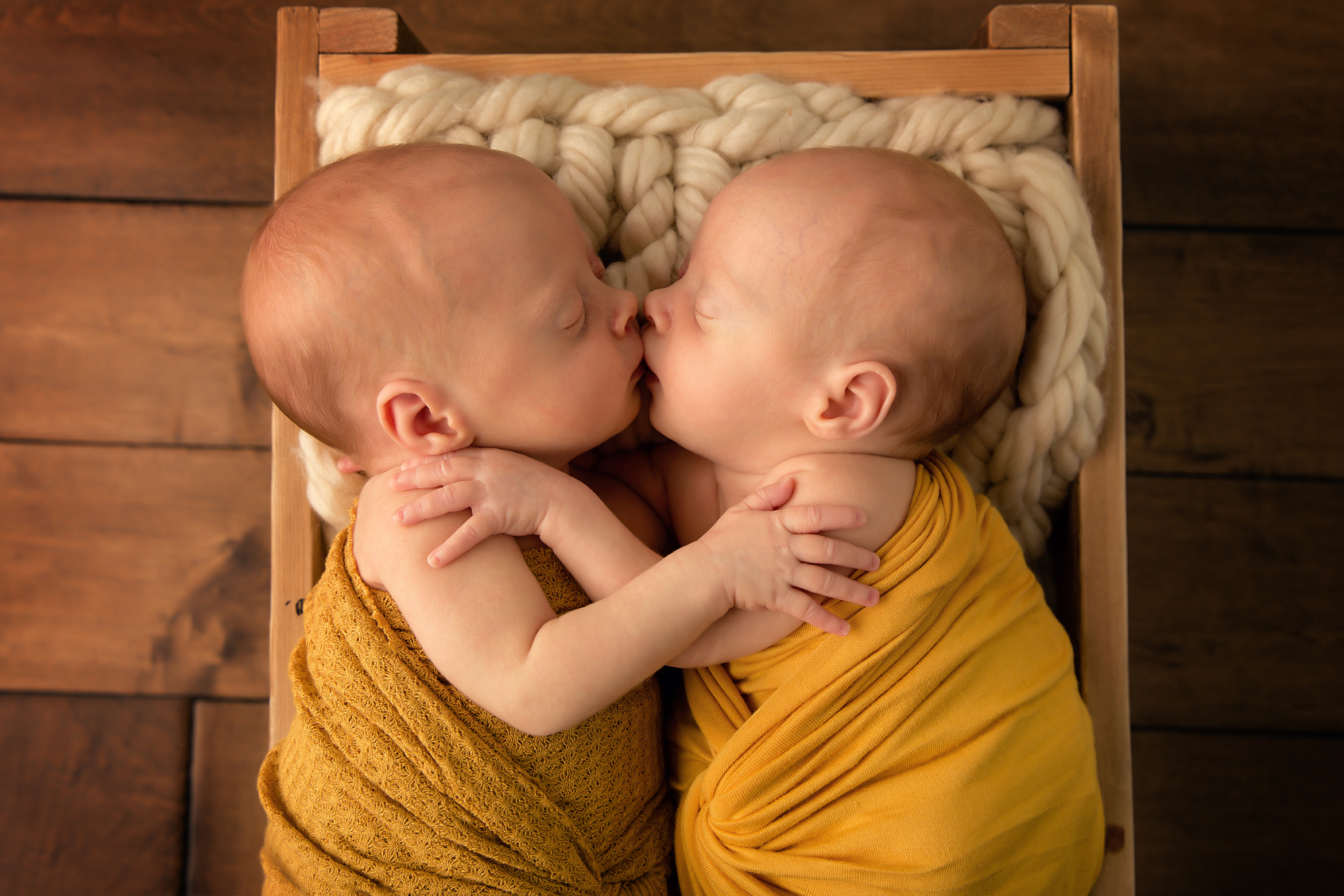 Twins Photography in Calgary, Alberta by Milashka Photography. Twin sisters are giving each other a kiss and a hug