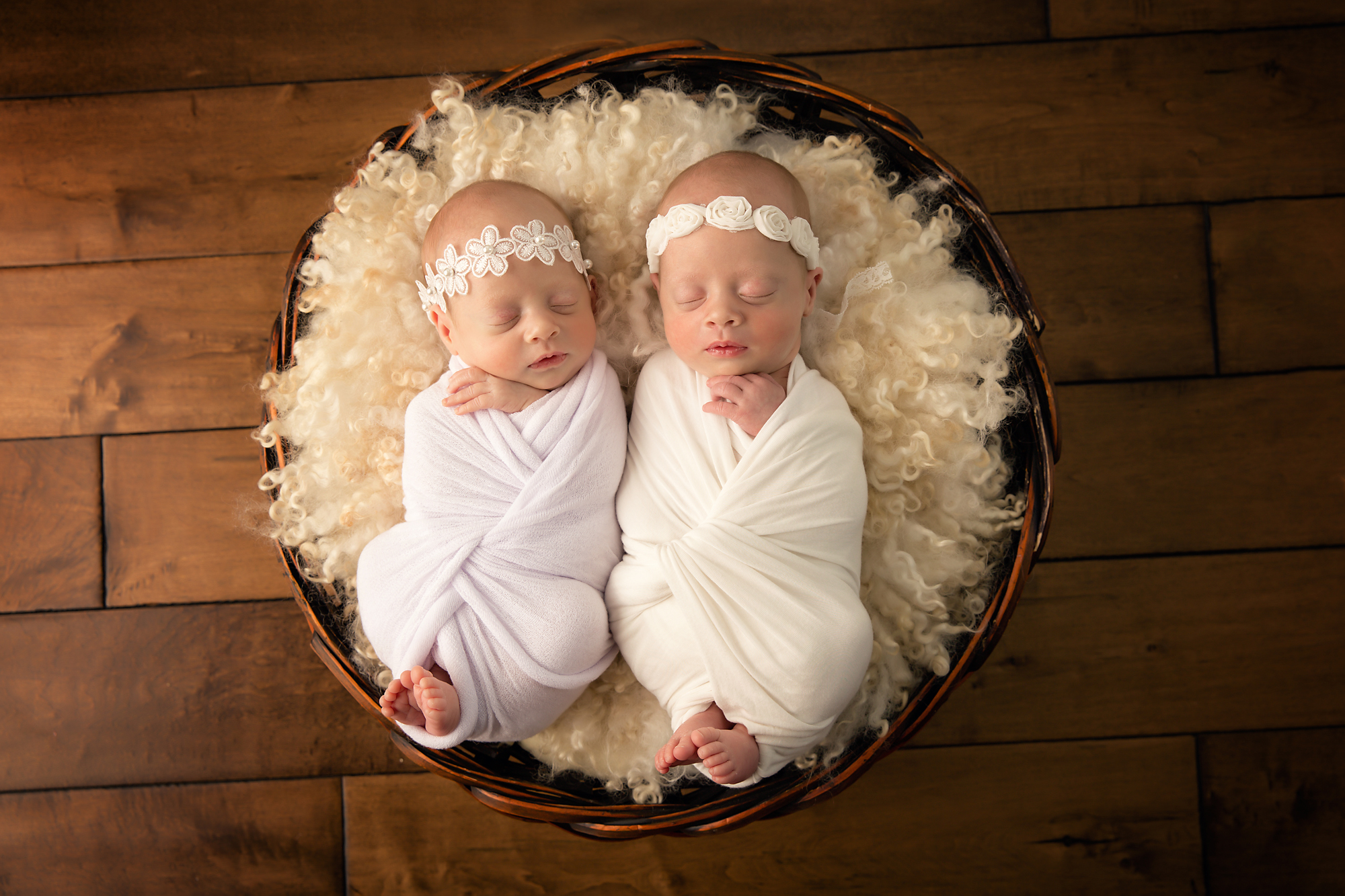 Twins Photography in Calgary, Alberta by Milashka Photography. Newborn Twin sisters are posed in a round basket and wrapped in white.