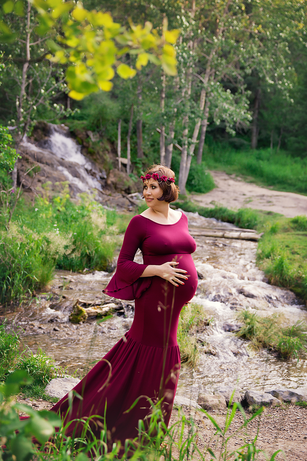 Mom-to-be is wearing a red gown and is looking playfully. Maternity photoshoot ideas. Calgary and Airdrie Maternity photographer