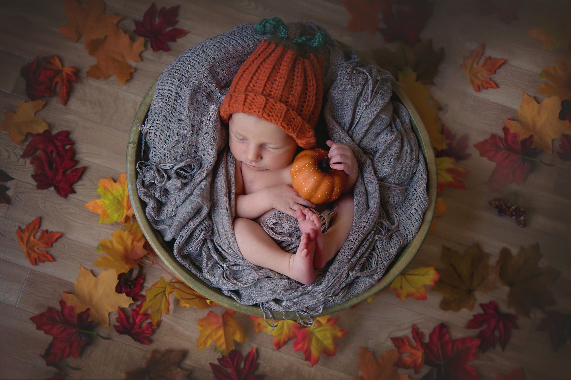 Thanksgiving inspired newborn baby photoshoot. Baby is dressed in a pumpkin hat, holding a little pumpkin, surrounded by leafs and is sleeping soundly in a wooden bowl. Newborn Photoshoot ideas. Calgary and Airdrie newborn baby photographer - Milashka Photography