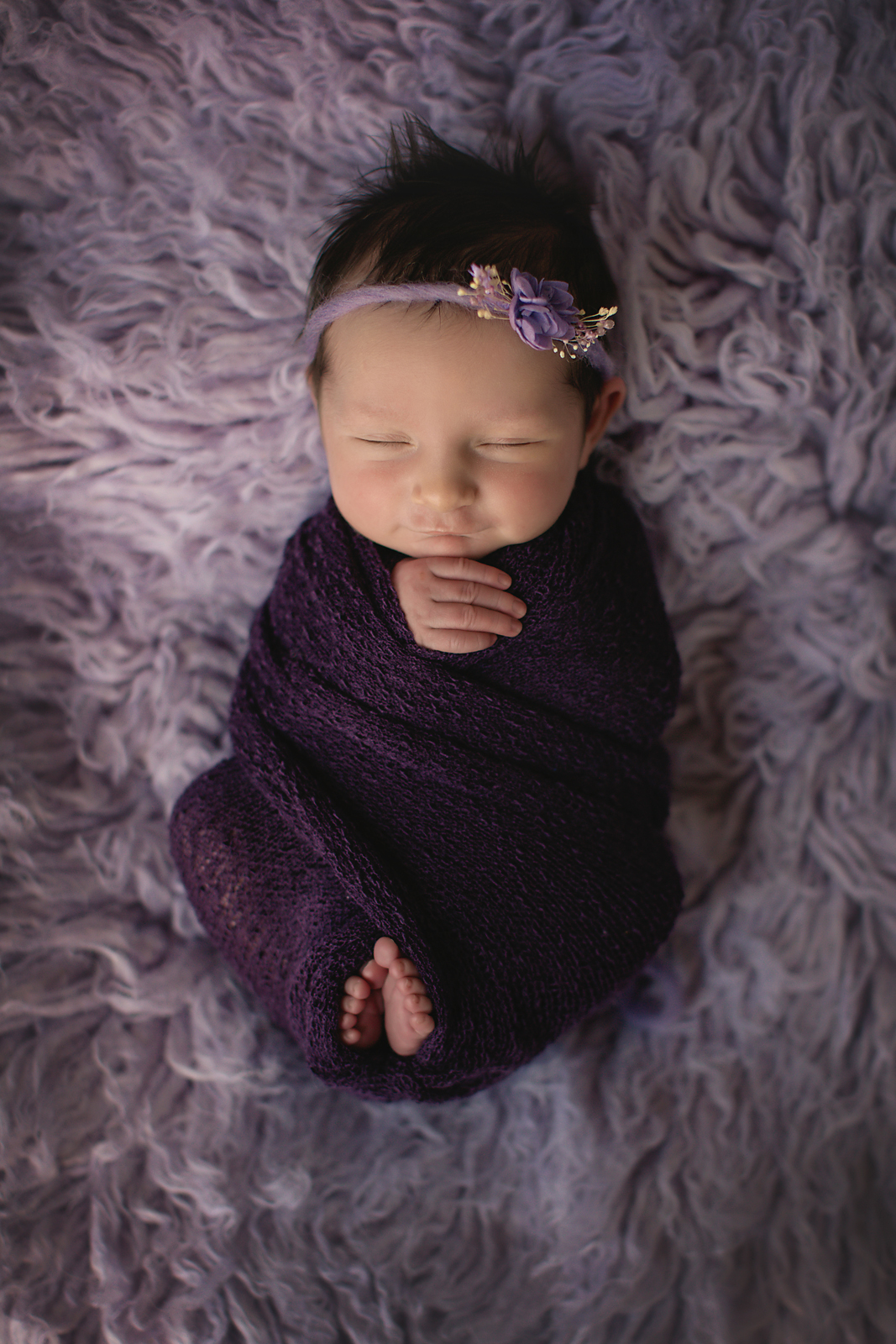 Smiling baby in a purple wrap on a purple rug. Newborn Photoshoot ideas. Calgary and Airdrie newborn baby photographer - Milashka Photography