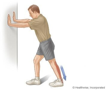 Standing Hamstring Stretch - 1. Using a wall or stable fixture, begin by taking a step backward.2. Straighten the back leg by extending the knee, pressing your heel down into the ground.3. Shift your hips forward to increase the stretch.