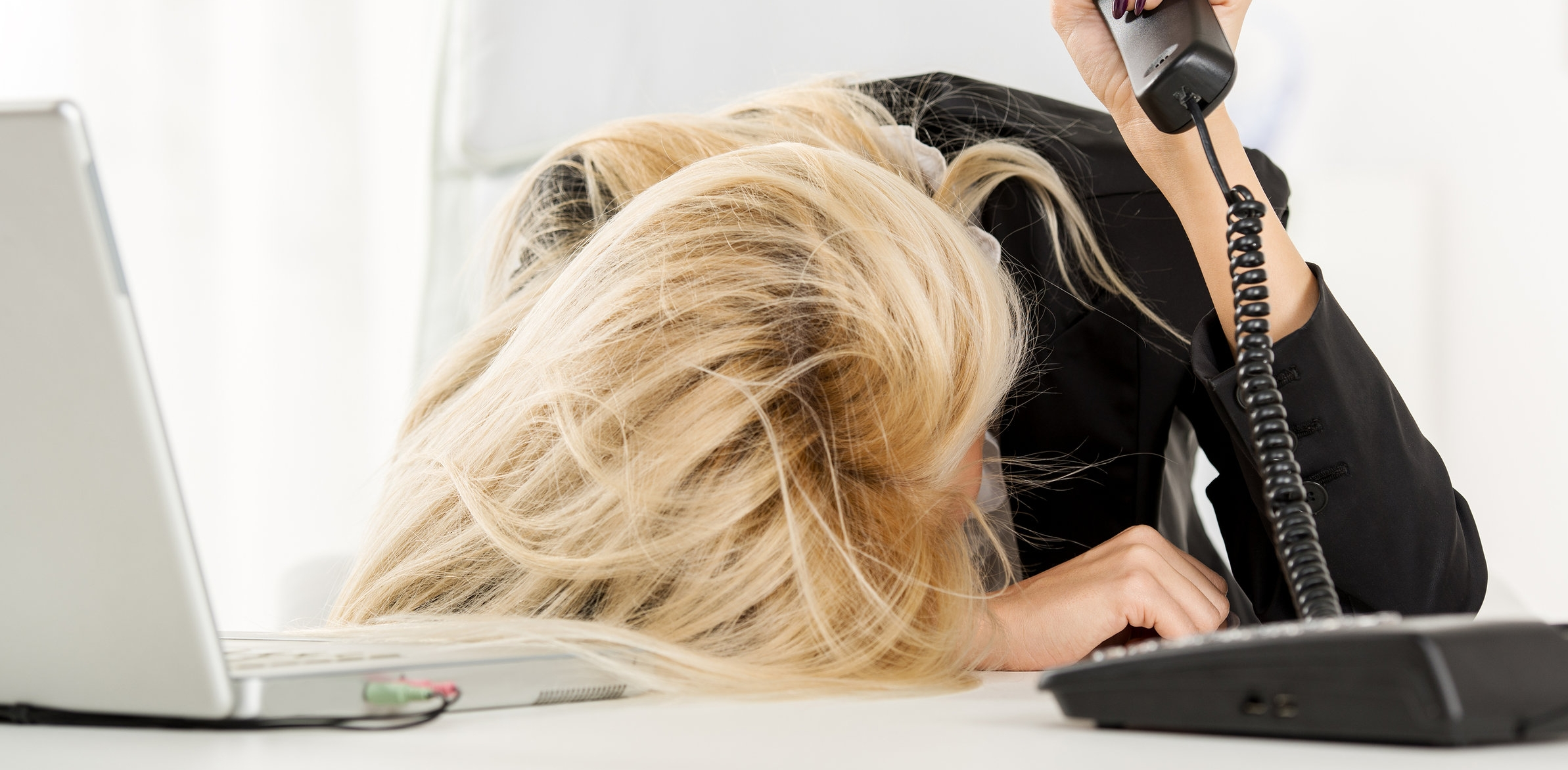 Frustrated business woman with head on desk