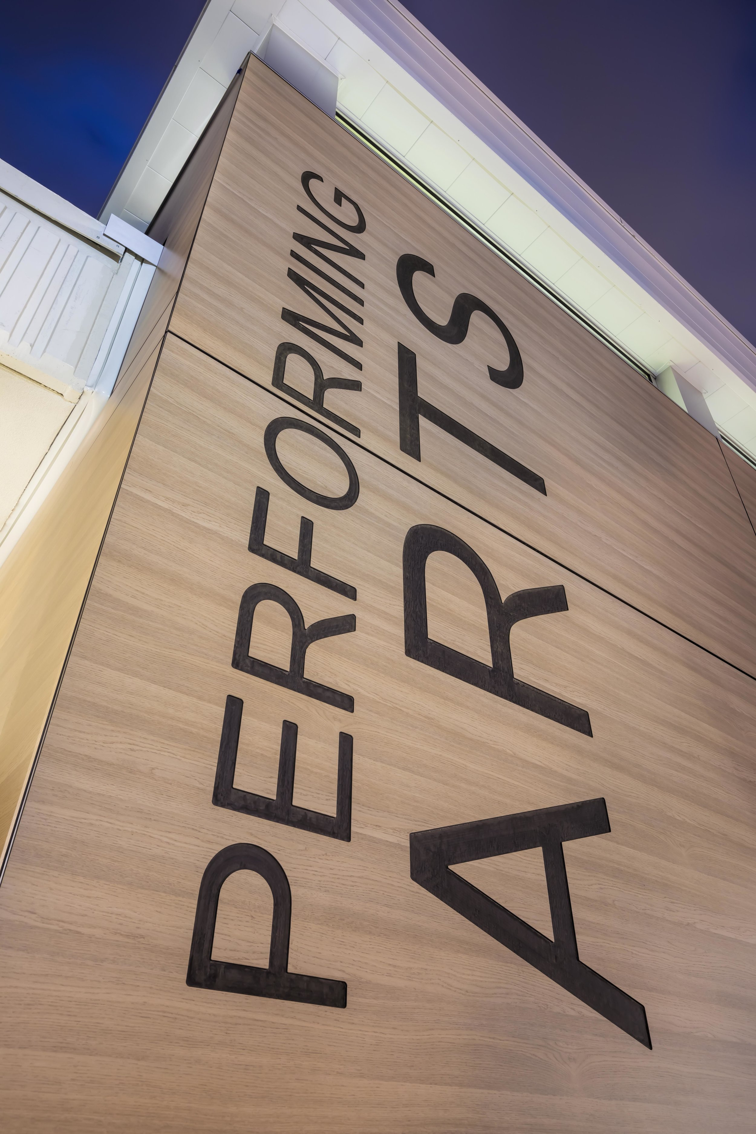 """Put it in Writing   Exterior Trespa panels were CNC milled with the words """"Performing Arts"""" reflecting the support by the District and Campus towards this art form."""