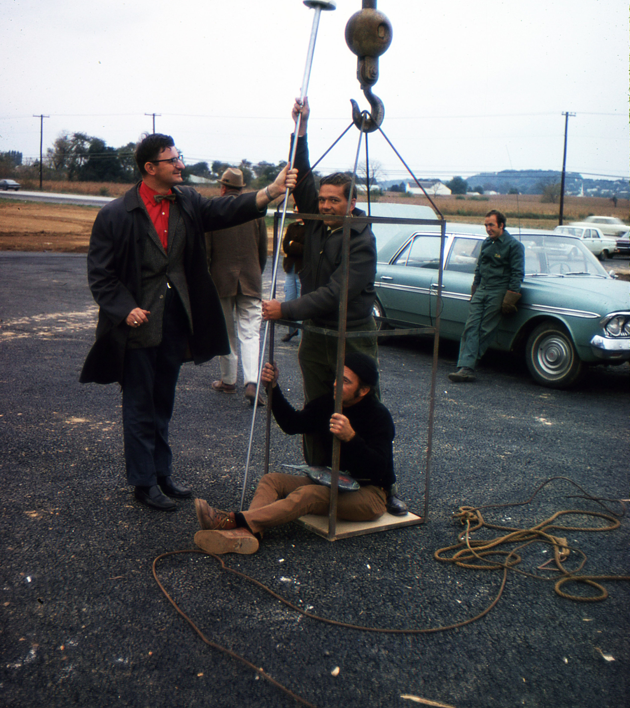 Skip Loose being put in the crane bucket preparing to place the fish at the top of the steeple spire, October 1970