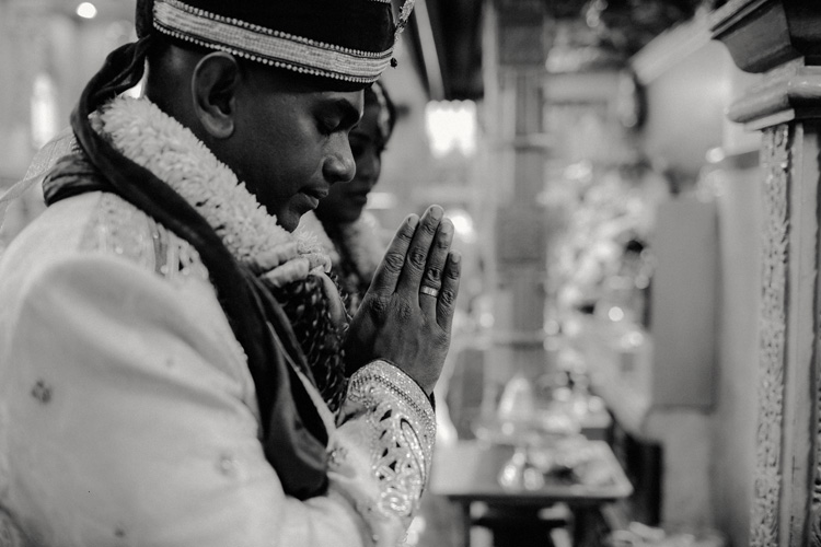 indian groom prays to god in hindu temple