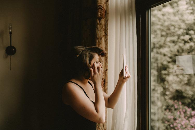 bride looks into mirror during bridal prep