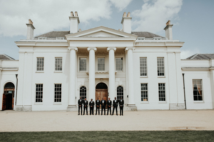 groomsmen stand in front of hylands house