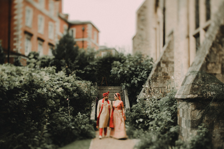indian couple hold hands in church garden after traditional wedding