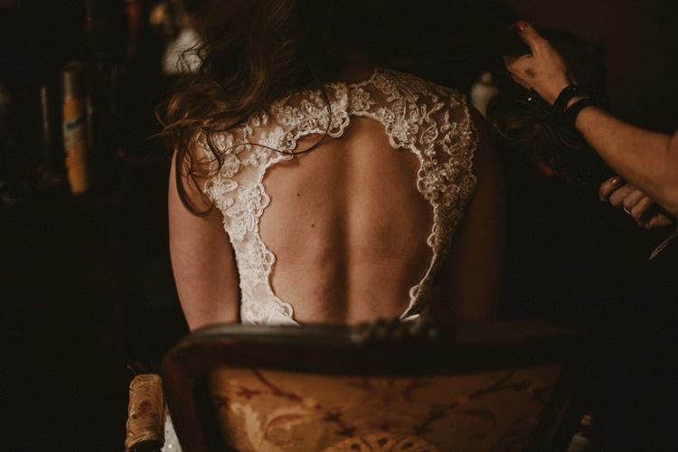 bride in vintage dress gets her hair done during bridal prep