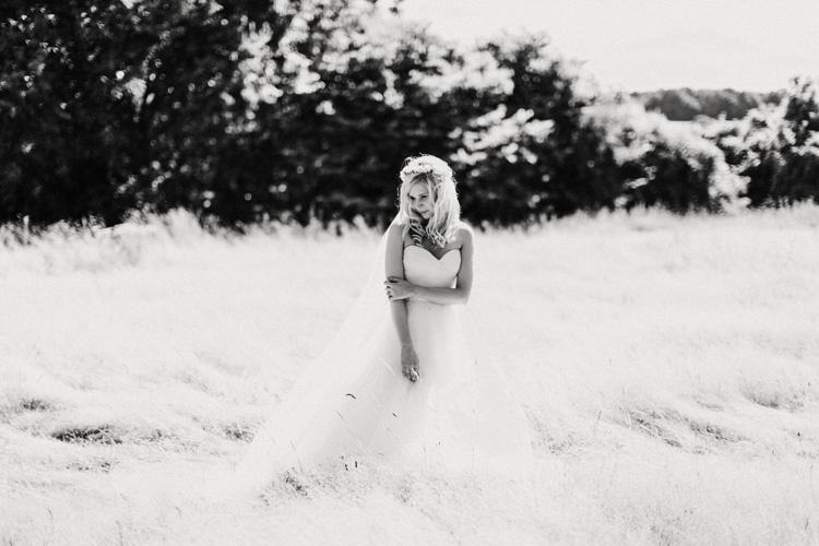 boho bride stands in hay field in chesham wedding