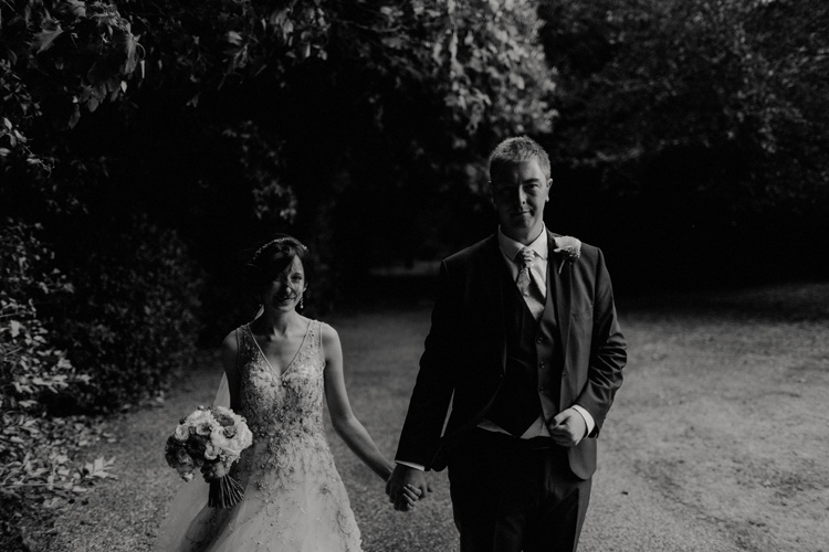 bride and groom holding hand in the wind in quex park wedding