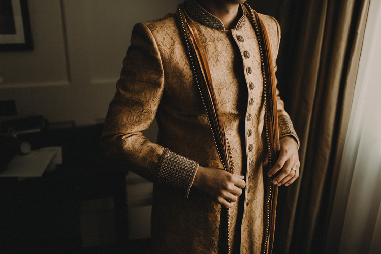 indian groom finishes getting ready before hindu ceremony