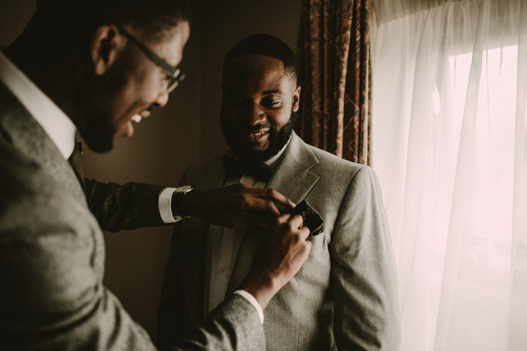 best man helps groom to get ready in froyle park wedding