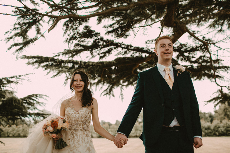 bride and groom holding hands after ceremony at quex park wedding