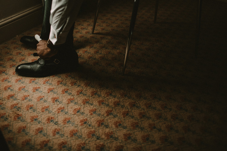 groom ties his laces whilst getting ready for froyle park wedding