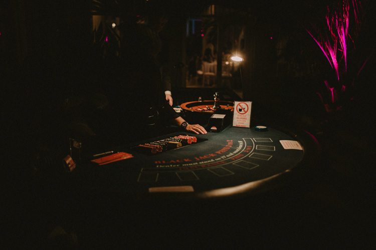 card dealer serves cards for poker game at syon park wedding